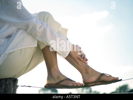 Woman sitting on wooden post resting feet on wire