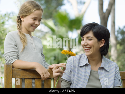 Mother and daughter, mother holding flower - Stock Photo