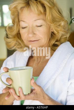 Senior woman in bathrobe holding mug