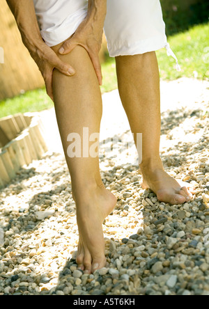 Senior woman holding leg, low section - Stock Photo