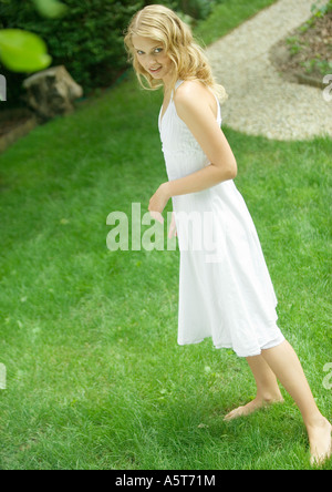 Young woman wearing white dress, standing barefoot on grass - Stock Photo