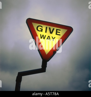 A lit up 'Give Way' warning road sign against a dark gray sky UK  KATHY DEWITT - Stock Photo