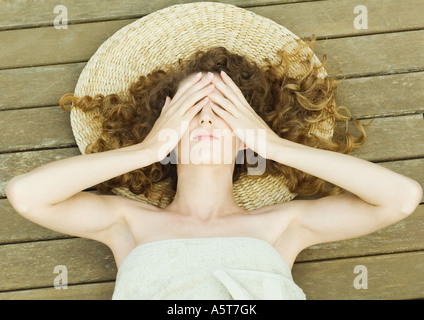 Woman lying on deck, wrapped in towel, head on mat, hands over eyes - Stock Photo