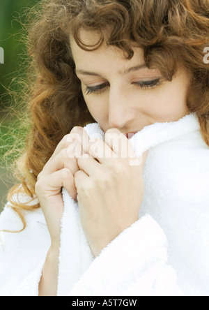 Woman wearing bathrobe, holding up edges of collar - Stock Photo