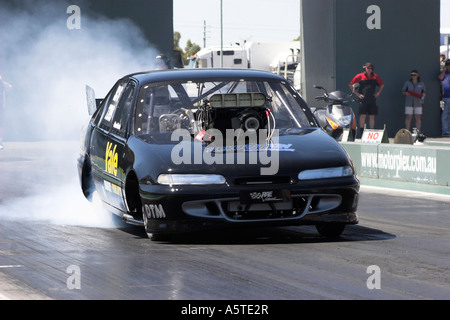 Australian Holden Commodore Supercharged Outlaws drag car performing smoky burnout on quarter mile race track - Stock Photo