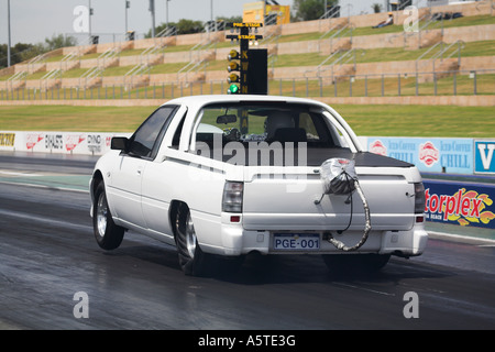 Holden pick up truck (called a utility in Australia) launching on the green light at the start of a drag race - Stock Photo