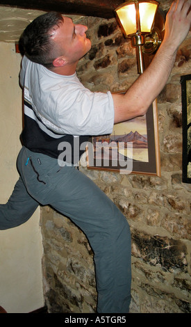 Young man indoor climbing the walls in an Inn after a few beers during a stag party weekend - Stock Photo