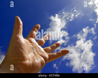 Male hand stretching up to a blue sky with clouds - Stock Photo