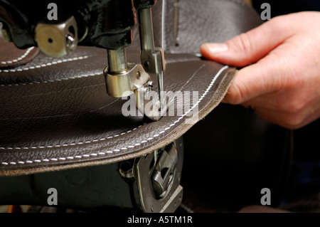 stitching leather on race horse saddle - Stock Photo