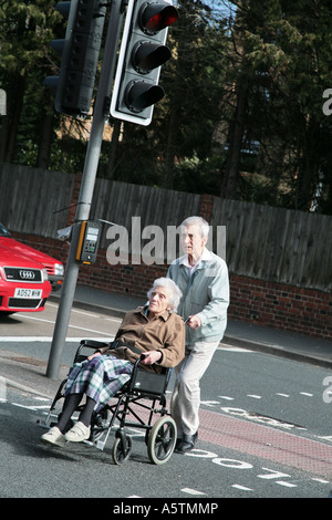 man pushing woman in wheelchair across road - Stock Photo