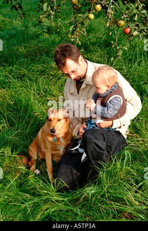 MR PR father with his baby boy and his dog on a meadow - Stock Photo