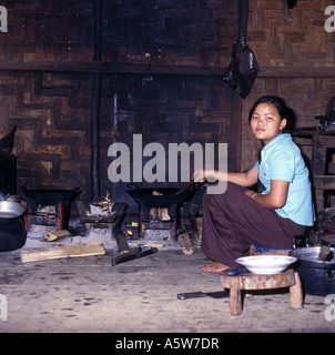 Local woman cooking over open fire in traditional rural kitchen,small village,North Laos. - Stock Photo