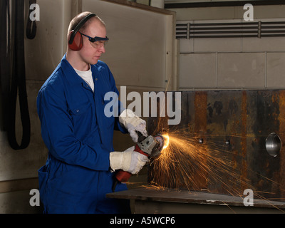Man wearing protective gloves goggles and ear protectors using angle grinder on iron block sparks heat friction - Stock Photo