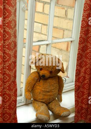 Old Fashioned Teddy Bear on a Georgian Window Sill - Stock Photo