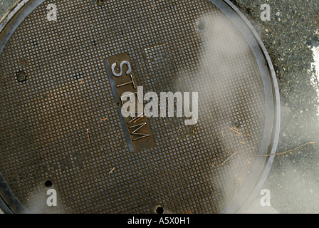 A manhole cover lets out steam in downtown Seattle on February 5, 2006. - Stock Photo