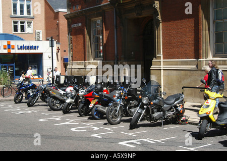 Motorcycles parked in a designated parking area on a city street. - Stock Photo