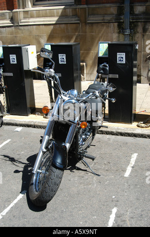 A motorcycle parked in a designated parking area on a city street in the UK - Stock Photo