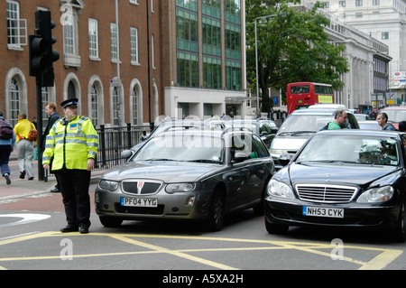 Community Support officer directing traffic in London England - Stock Photo
