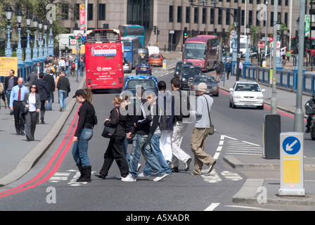 people crossing the road using a zebra crossing in the city of london, england - Stock Photo
