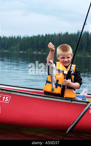 5 year old boy in red canoe holding up fish - Stock Photo