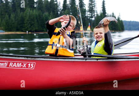 5 and 6 year old cousins in red canoe holding up fish - Stock Photo