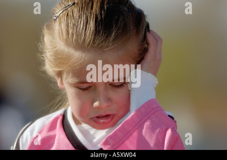 Young girl in Soccer uniform looking sad and crying - Stock Photo