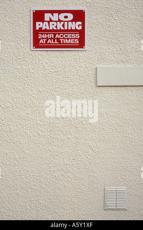 Red and white sign high up on a cream painted rendered wall stating No parking 24 hr access at all times - Stock Photo