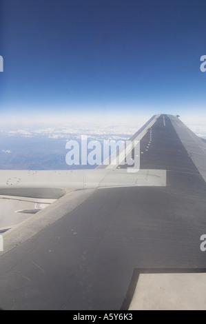 Aircraft wing airplane wing airplane flying showing horizon and blue sky above clouds - Stock Photo