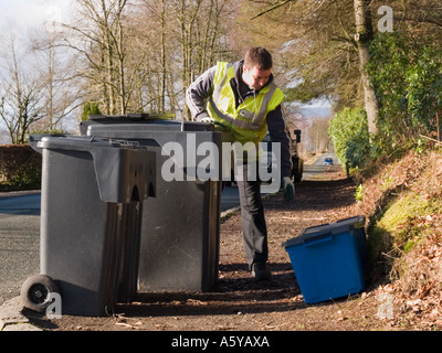 Man collecting kerbside re-cycling boxes beside 2 wheelie bins of household waste on roadside on bin collection - Stock Photo