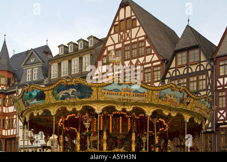 Christmas fair on the square Roemer Römer old merry go round in front of storefronts of half timbered houses in - Stock Photo