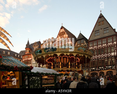 Christmas fair on the square Roemer Römer old merry go round in front of storefronts of half timbered houses - Stock Photo