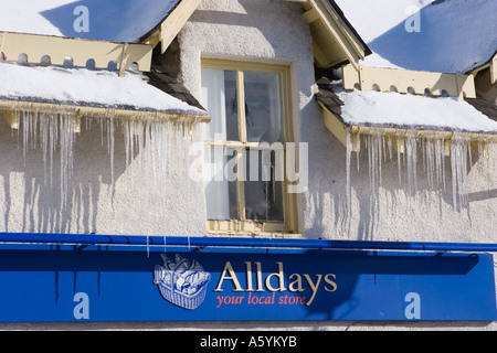 Roof covered in hard, pointed icicles on Alldays shop in Braemar Scotland uk in spring sunshine with icicles hanging - Stock Photo