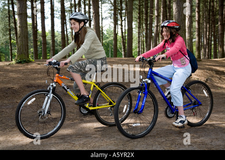 Two teenage girls cycling in Delamere Forest Cheshire - Stock Photo