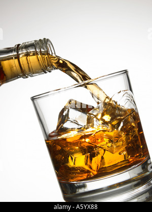 WHISKEY POURING FROM BOTTLE ONTO ICE CUBES IN GLASS TUMBLER - Stock Photo