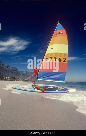 CAMPS BAY HOBIE CAT Girl poses on Hobie Cat with colourful sail on sandy coastline at Camps Bay Beach South Africa - Stock Photo
