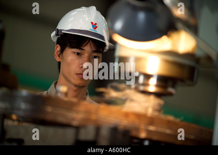 Apprentice Vietnamese shipyard worker, in engineering workshop, Vietnam, Asia - Stock Photo