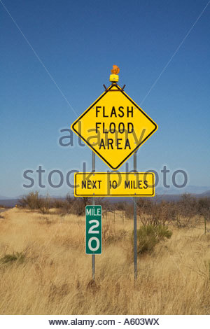 Highway warning sign Flash Flood Area Next 10 Miles warns of heavy water flows after thunderstorms in dips - Stock Photo