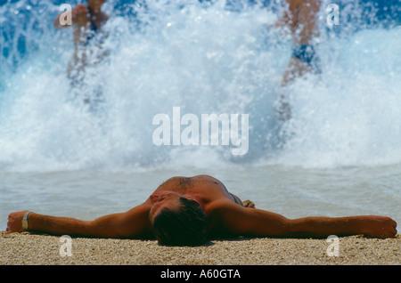 sunbather on Kaputas beach south coast nr Kas Turkey - Stock Photo