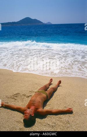sunbather on Kaputas beach south coast near Kas Turkey - Stock Photo