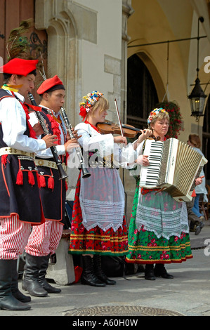 Vertical close up of costumed musicians playing infront of the 'Sukiennice' Cloth Hall in the Main Market Square - Stock Photo