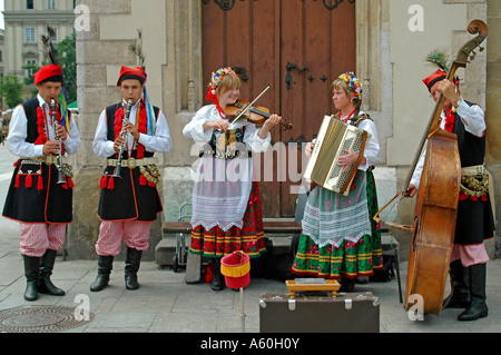 Horizontal close up of costumed musicians infront of the 'Sukiennice' Cloth Hall in the Market Square 'Rynek Glowny' - Stock Photo