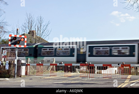 A train passing over a road crossing in Surrey, UK. - Stock Photo