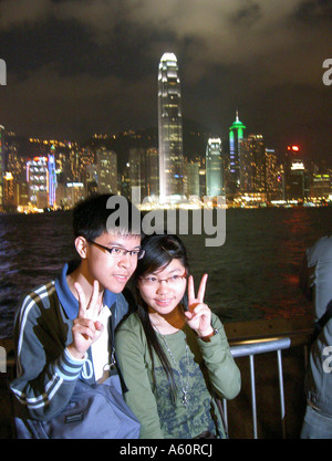 Chinese couple posing for photo. Hong Kong skyline. Tallest is Two International Finance Centre seen over harbour - Stock Photo
