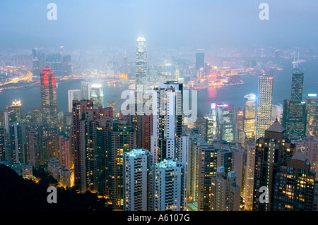 Hong Kong Island. Dusk view from Victoria Peak over city centre skyscrapers and Hong Kong Harbour to Kowloon shore - Stock Photo