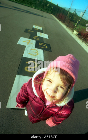 A young child playing hopscotch in a childrens playground - Stock Photo
