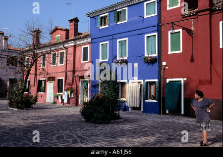 Middle aged woman waiting at the front of a villa on the Island of Burano, Venice, Italy. - Stock Photo