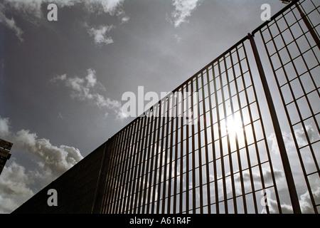 sun breaking through grid fence  - Stock Photo