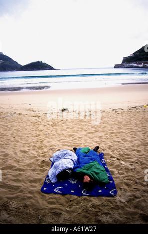 Refugees sleeping on a beach, San Sebastian, northern Spain - Stock Photo