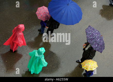 Spectators wearing rain ponchos and holding umbrellas brave the rain to watch the Passion precession in Chicago. - Stock Photo