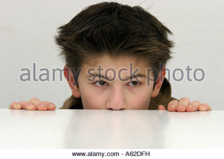 portrait of a young boy looking over the edge of a table - Stock Photo